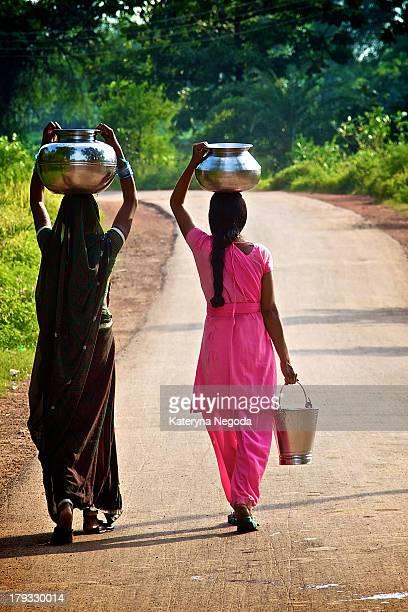 Sari-clad women in Raipur, India, balancing baskets of water on their head.