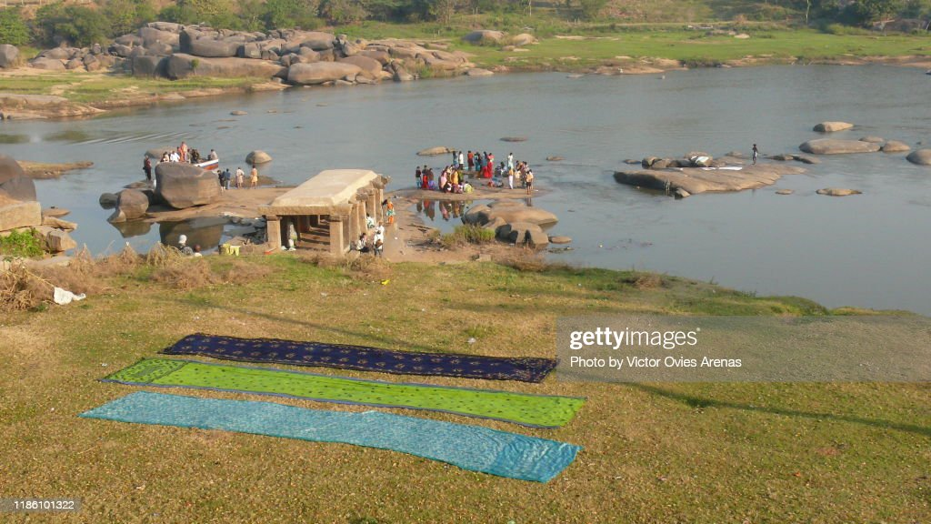 Saris laying on the ground drying in the sun and morning activity and ablutions in the Tungabhadra River in Hampi, Karnataka, India : Foto de stock