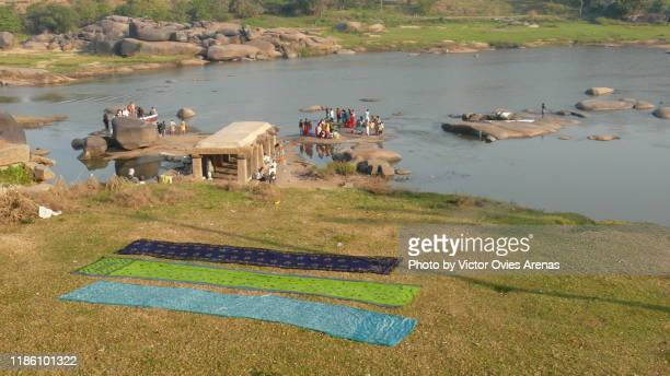 saris laying on the ground drying in the sun and morning activity and ablutions in the tungabhadra river in hampi, karnataka, india - victor ovies fotografías e imágenes de stock