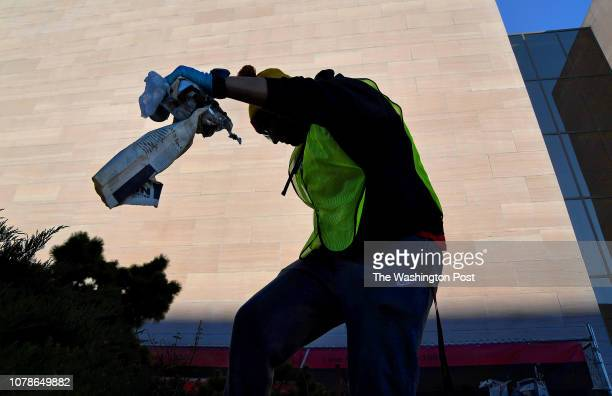 Sarmad Bhatti pulls a handful of trash from a garden area outside the National Air and Space Museum Due to the partial government shutdown some...