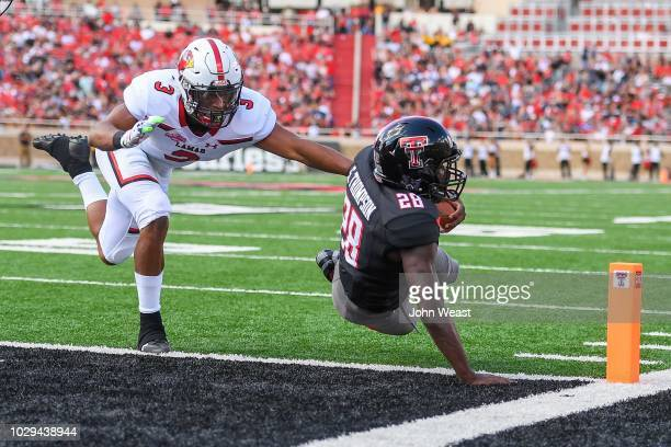 SaRodorick Thompson of the Texas Tech Red Raiders dives for the end zone against Garrison Mitchell of the Lamar Cardinals during the first half of...