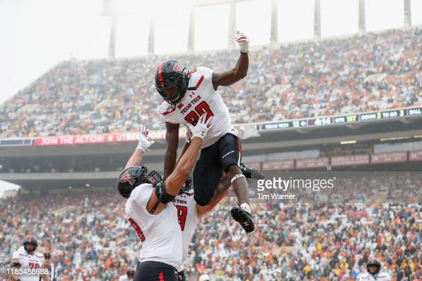 SaRodorick Thompson of the Texas Tech Red Raiders is lifted in celebration by teammates after a touchdown in the first quarter against the Texas...