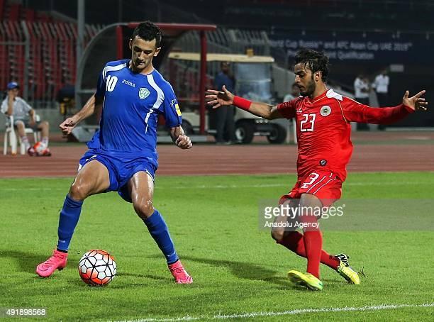 Sarsdor Rashidov of Uzbekistan vies with Rashed elHuti of Bahrain during the 2018 FIFA World Cup Round 2 Group H qualification match between Bahrain...