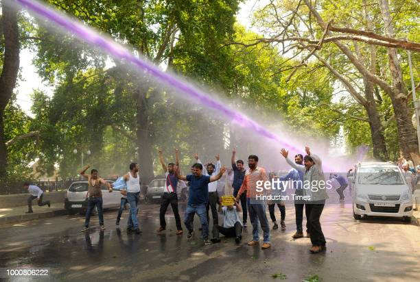 Sarva Shiksha Abhiyan teachers raise slogans as police spray purple colored water to disperse a protest in Lal chowk area on July 17 2018 in Srinagar...