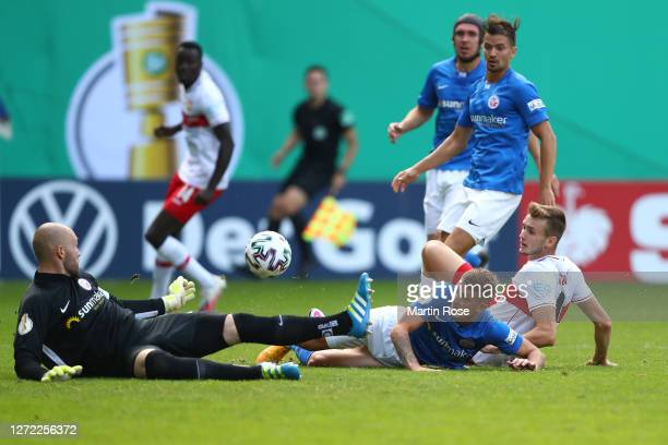Sasa Kalajdzic of Stuttgart tries to score against Nico Neidhart and goalkeeper Markus Kolke of Rostock during the DFB Cup first round match between...