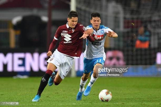 Sasa Lukic of Torino FC is challenged by Hirving Lozano of SSC Napoli during the Serie A match between Torino FC and SSC Napoli at Stadio Olimpico di...