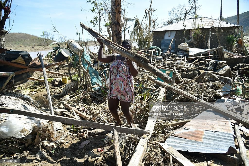 Sasa, 25, takes the remains of her house destroyed by Hurricane Matthew, to build another in a nearby field in Jeremie, Haiti, on October 8, 2016. The full scale of the devastation in hurricane-hit rural Haiti became clear Saturday as the death toll surged past 400, three days after Matthew leveled huge swaths of the country's south. / AFP / HECTOR