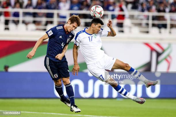 Sasaki Sho of Japan competes for the ball with Dostonbek Khamdamov of Uzbekistan during the AFC Asian Cup Group F match between Japan and Uzbekistsn...