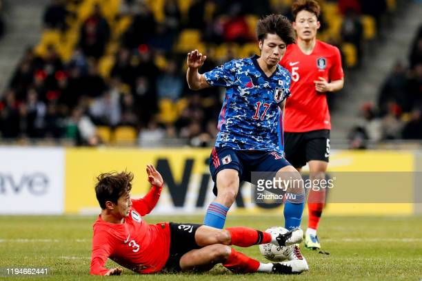 Sasaki Sho of South Korea competes for the ball with Kim Jinsu of Japan during the EAFF E-1 Football Championship match between South Korea and Japan...