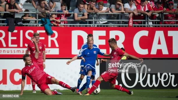 Sascha Bigalke of Unterhaching challenges Sebastian Schuppan of Wuerzburg and Bjoern Jopek of Wuerzburg during the 3. Liga match between FC...
