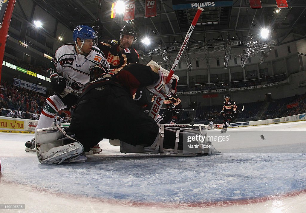 Sascha Goc (L) of Hannover and Sergio Somma (R) of Augsburg battle for the puck during the DEL match between Hannover Scorpions and Augsburger Panther at TUI Arena at TUI Arena on January 9, 2013 in Hanover, Germany.