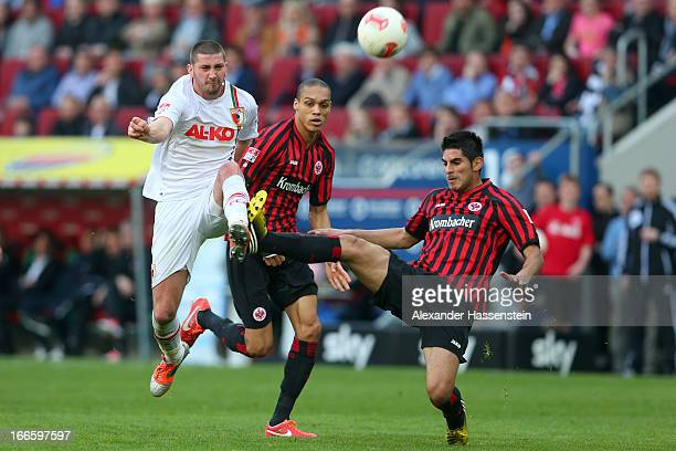 Sascha Moelders of Augsburg battles for the ball with Carlos Zambrano of Frankfurt and his team mate Oliveira Andreson-De during the Bundesliga match...