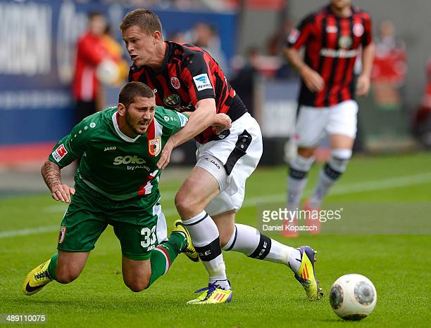Sascha Moelders of Augsburg is challenged by Alexander Madlung of Frankfurt during the Bundesliga match between FC Augsburg and Eintracht Frankfurt...