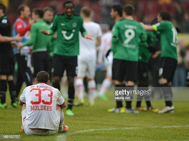 Sascha Moelders of Augsburg sits on the ground while the players of Hannover celebrate their win after the Bundesliga match between FC Augsburg and...