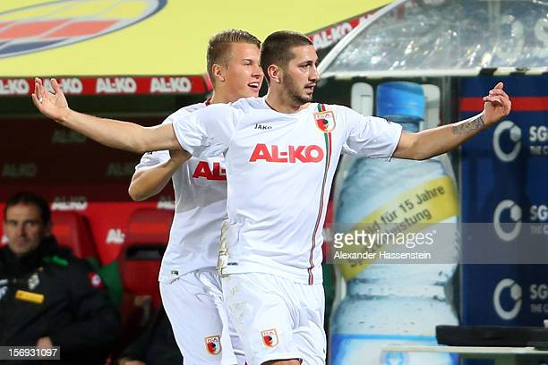 Sascha Moelders of Ausgbsurg celebrates scoring the opening goal with his team mate Matthias Ostrzolek during the Bundesliga match between FC...