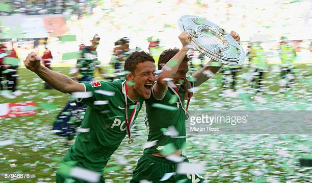 Sascha Riether and Christian Gentner of Wolfsburg celebrate the German championship with the trophy after their Bundesliga match against SV Werder...