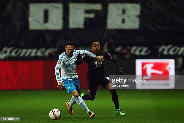 Sascha Riether of Schalke is challenged by Marco Fabian of Frankfurt during the Bundesliga match between Eintracht Frankfurt and FC Schalke 04 at...