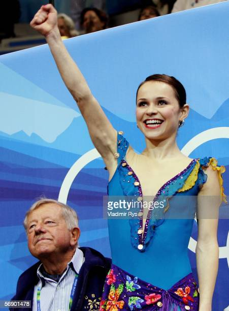 Sasha Cohen of the United States sits next to her coach as she reacts to her score after she performed during the women's Short Program of the figure...