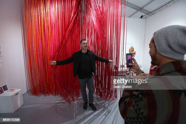 Sasha Gjorsovski poses with an installation titled 'The Sun Has Burnt the Sky' by Anne Patterson on exhibit at Scope Art Fair during Art Basel Miami...
