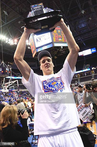 Sasha Kaun of the Kansas Jayhawks hoists the trophy following the Jayhawks victory in the finals of the Phillips 66 Big 12 Men's Basketball...