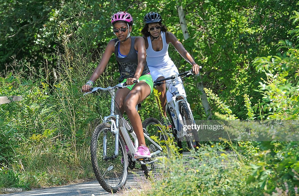 Sasha Obama (L) and first lady Michelle Obama ride bikes during a vacation on Martha's Vineyard August 16, 2013in West Tisbury, Massachusetts. Obama and his family are on a weeklong vacation.