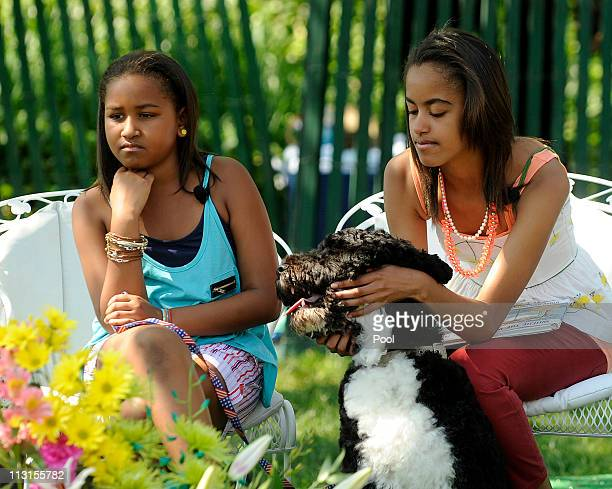Sasha Obama and Malia Obama play with their dog Bo as they listen to President Barack Obama read to children during the White House Easter Egg Roll...