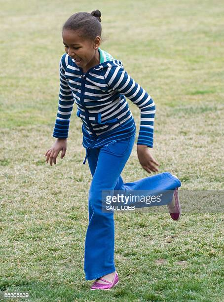 Sasha Obama daughter of US President Barack Obama runs into the White House after arriving on Marine One on the South Lawn in Washington on March 8...