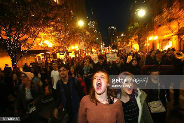 Sasha Savenko and Sydney Kane both students at the University of Washington join thousands of protesters march down 2nd Avenue on November 9 2016 in...