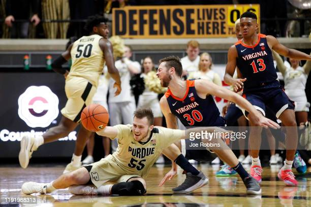 Sasha Stefanovic of the Purdue Boilermakers tries to recover the ball after running into Jay Huff of the Virginia Cavaliers in the first half at...
