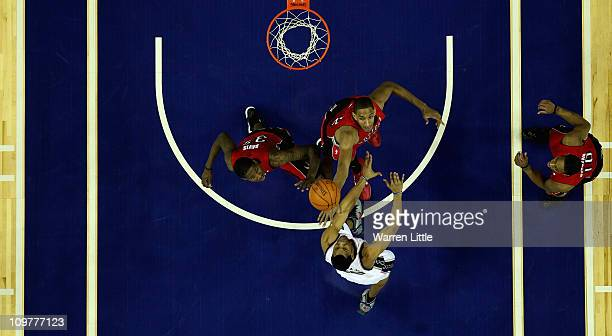 Sasha Vujacic of the Nets jumps against Alexis Ajinca and Ed Davis of the Raptors during the NBA match between New Jersey Nets and the Toronto...