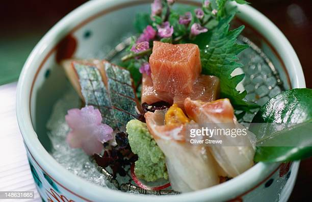 Sashimi from the Miyako Hotel in Kyoto. Sashimi includes tuna, sea urchin and horse mackerel, served on a bed of rice with beefsteak plant flower for decoration.