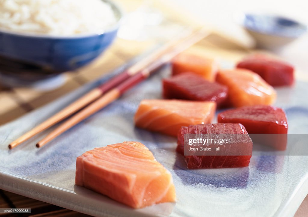 Sashimi on plate with chopsticks, bowl of rice in background, close-up : Foto de stock