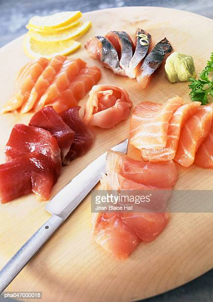Sashimi with wasabi and lemon slices on wooden board