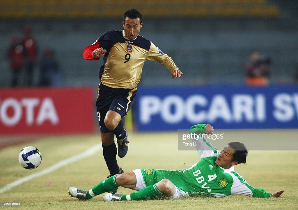 Sasho Petrovski (L) of Newcastle Jets is tackled by Zhou Ting of Beijing Guoan during the AFC Champions League Group E match between Beijing Guoan and the Newcastle Jets at Beijing Worker's Stadium on March 10, 2009 in Beijing, China.