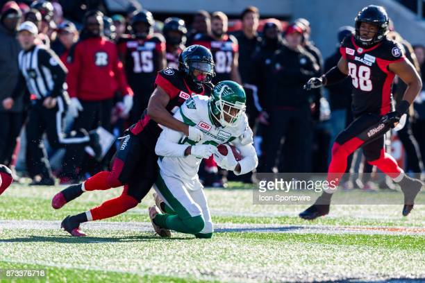 Saskatchewan Roughriders wide receiver Duron Carter is tackled by Ottawa RedBlacks defensive back Corey Tindal during Canadian Football League...
