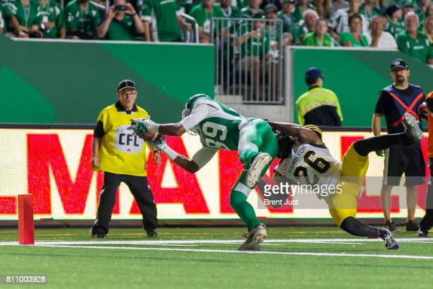 Saskatchewan Roughriders wide receiver Duron Carter reaches for the goal after making a catch but is denied by Hamilton TigerCats defensive back...