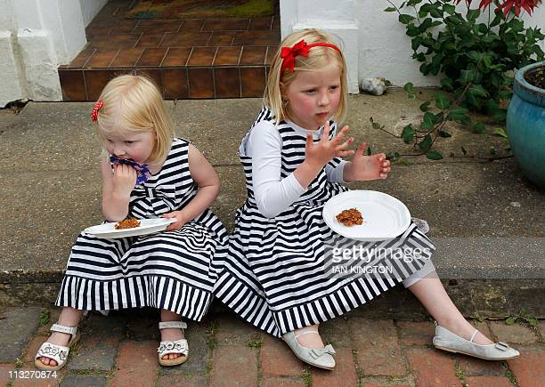 Saskia and Eva Williams enjoy the food during a street party in Tunbridge Wells southeast England celebrating the royal wedding between Britain's...
