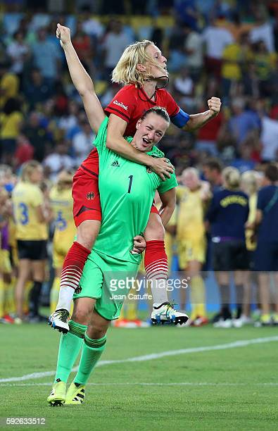 Saskia Bartusiak and goalkeeper of Germany Almuth Schult of Germany celebrate winning the gold medal in the Women's Soccer Final between Germany and...