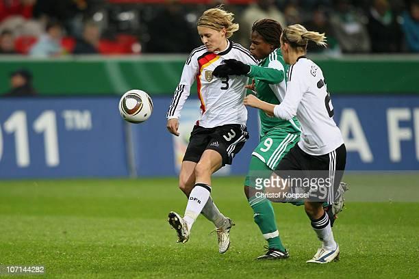 Saskia Bartusiak of Germany and Lena Goessling of Germany challenge Desire Oparanozie of Nigeria during the women's international friendly match...