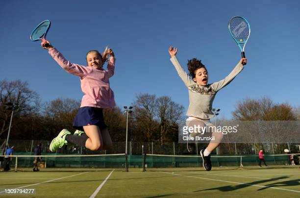 Saskia Brunskill and friend Ella leap with joy at the Sale sports club's tennis courts before their first group tennis coaching session since the...