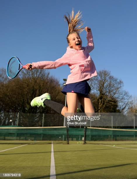 Saskia Brunskill leaps with joy at the Sale sports club's tennis courts before her first group tennis coaching session since the lockdown started in...