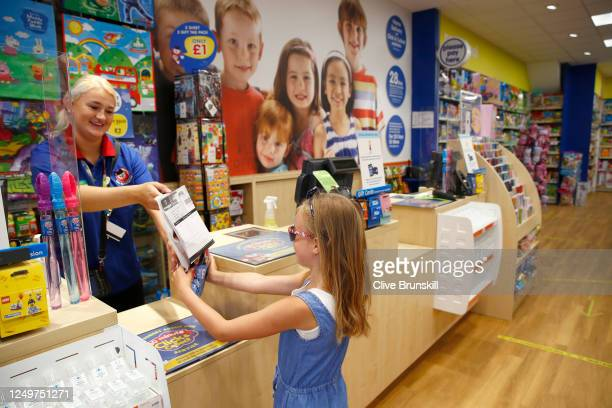 Saskia Brunskill the photographers daughter, buys a toy inside the Entertainer toy store on the first day of its official reopening on June 15, 2020...