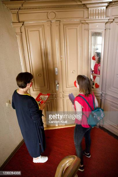Saskia Esken , co-head of the German Social Democrats , and parliament candidate Annika Klose stand in the stairwell of a residential building during...