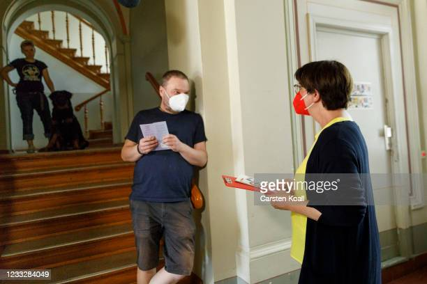 Saskia Esken, co-head of the German Social Democrats ,speaks to locals in the stairwell of a residential building during the launch of the SPD's...
