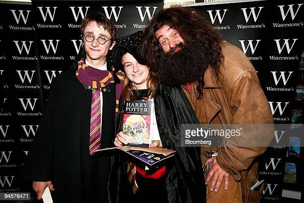 Saskia Haifierna center the first person to buy a copy of Harry Potter and the Deathly Hallows by JK Rowlings poses with fans dressed as Harry left...