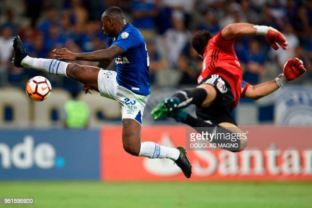 TOPSHOT Sassa of Brazil's Cruzeiro and goalkeeper Johnny Herrera of Chile's Universidad de Chile jump in the air for the ball during their Copa...