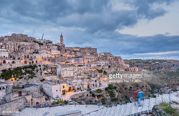 sassi di matera against cloudy sky at dusk - matera stock photos and pictures