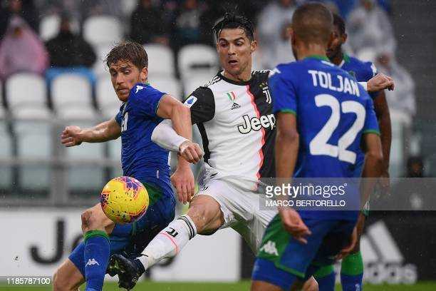 TOPSHOT Sassuolo's Brazilian defender Marlon fights for the ball with Juventus' Portuguese forward Cristiano Ronaldo during the Italian Serie A...