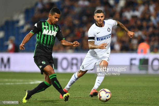 Sassuolo's Brazilian defender Rogerio passes the ball past Inter Milan's Argentine forward Mauro Icardi during the Italian Serie A football match...