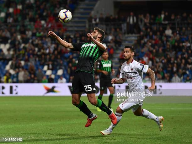 Sassuolo's forward Domenico Berardi chest controls the ball under pressure from AC Milan's Spanish forward Suso during the Italian Serie A football...